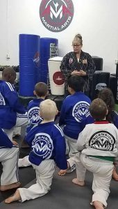 Kids listening to martial arts instructor at Ascension Martial Arts